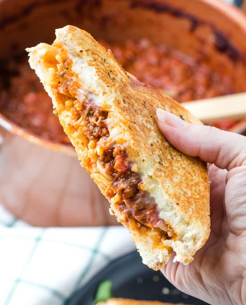 One half spaghetti sandwich held in hand