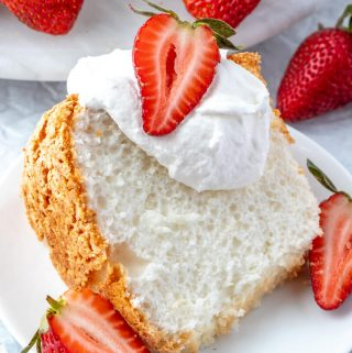 Slice of Angel Food Cake on white plate topped with whipped cream and strawberry