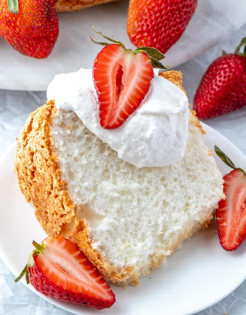 angel food cake recipe sliced on plate with whipped topping and strawberries