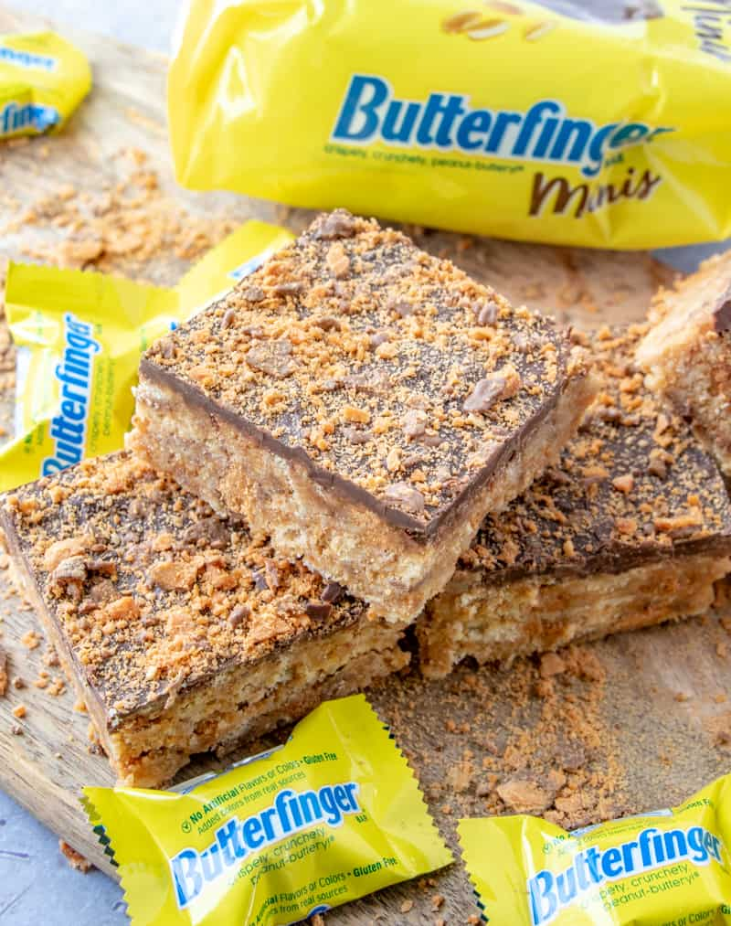 Butterfinger squares laid on top of one another on cutting board