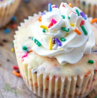 Close up of mini cheesecake in wrappers topped with whipped cream and rainbow sprinkles