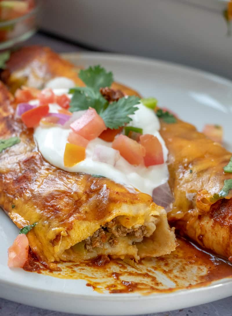 beef mixture showing on cut enchilada on plate with sour cream and pico de Gallo