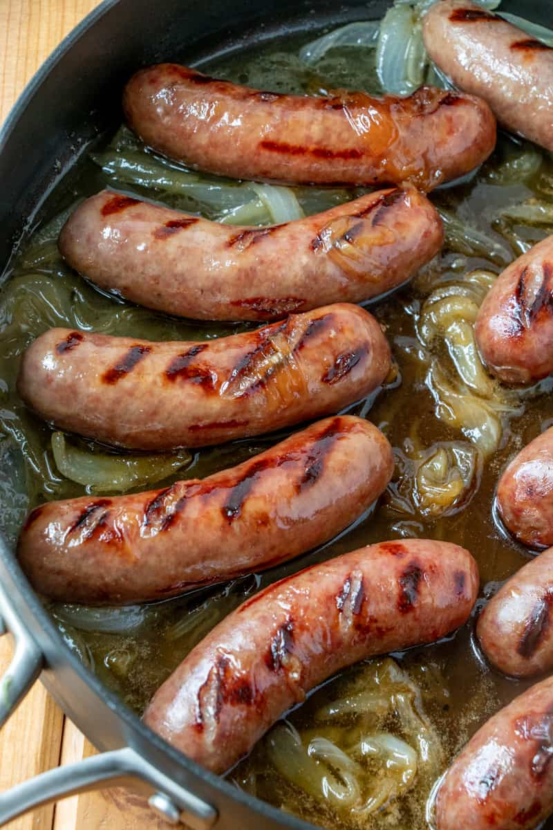 Grilled brats in pan with reduced beer and caramelized onions