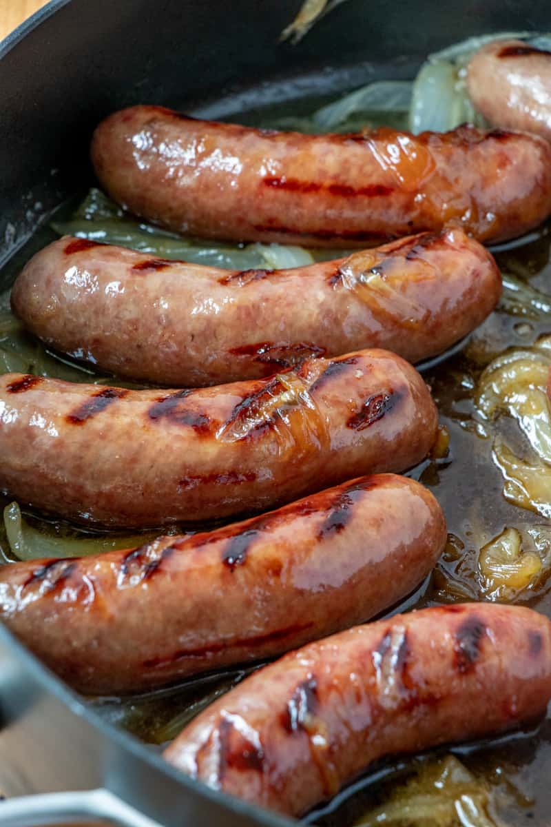 up close photo of cooked brats in caramelized onions in large pan with grill marks