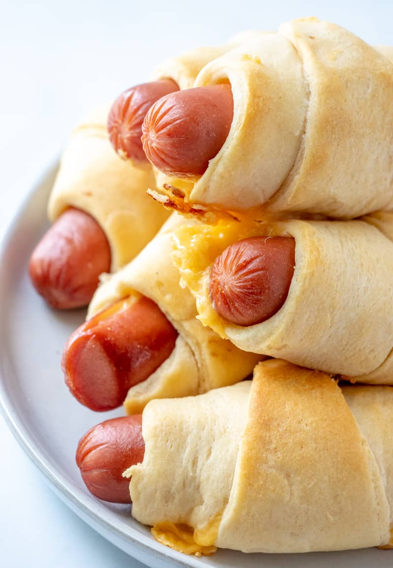 up close photo of hot dogs in crescent rolls layered on plate