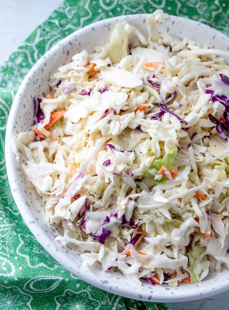 overhead photo of coleslaw in bowl with green fabric napkin