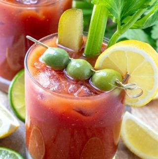 Bloody Mary Mix in glass with olives, pickle, celery and lemon slice