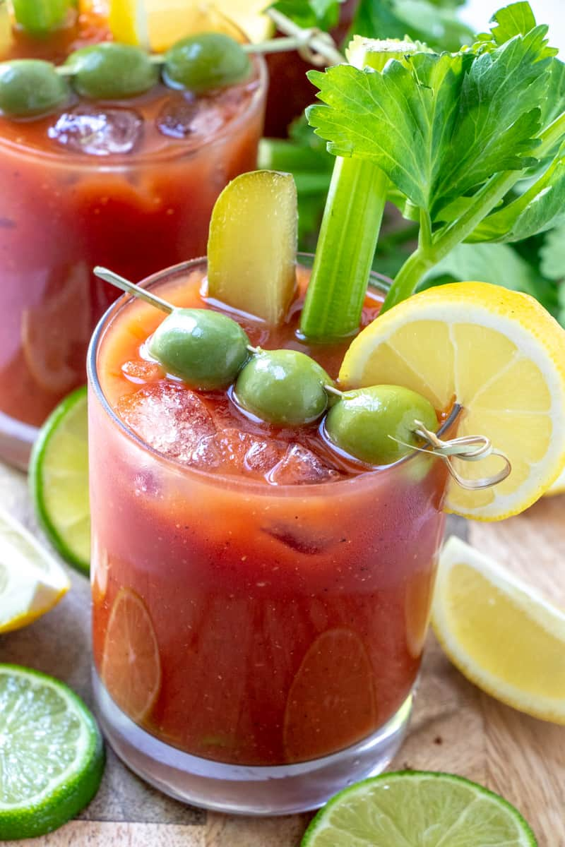 Bloody Mary mix dressed up with olives, lemon, pickle and celery in glass