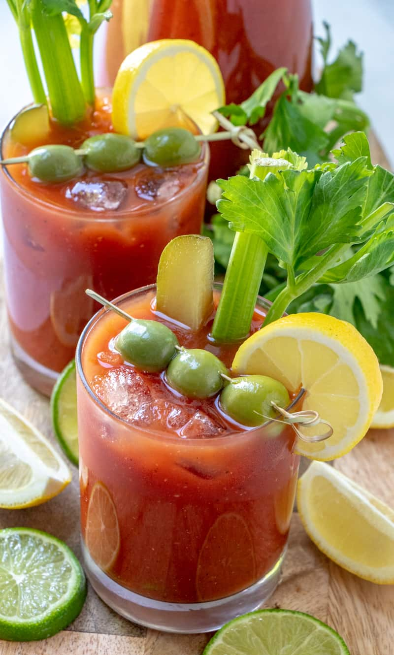 overhead photo of two ready to serve bloody Mary's dressed up with pitcher of mix in background