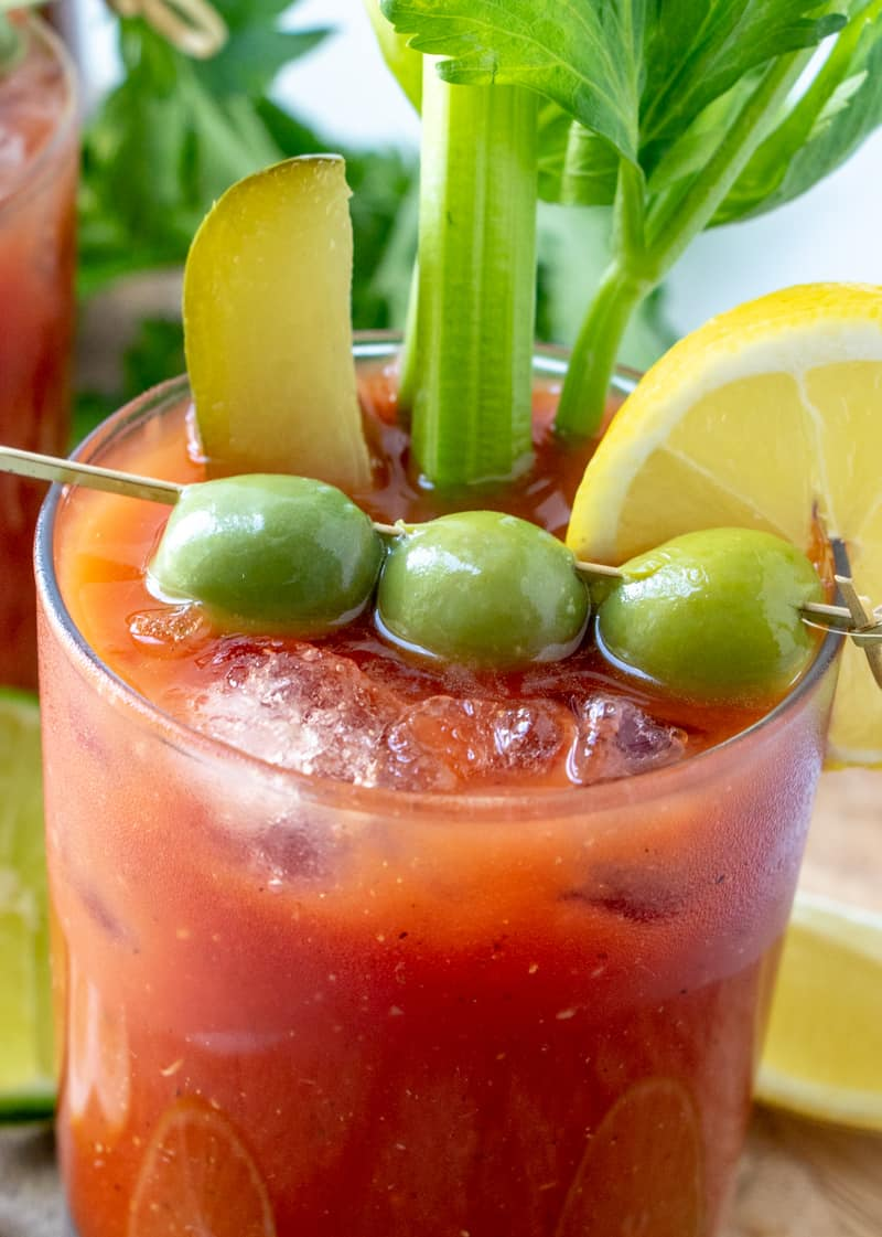 close up of Bloody Mary in glass ready to serve with ice, olives, pickle, celery and lemon