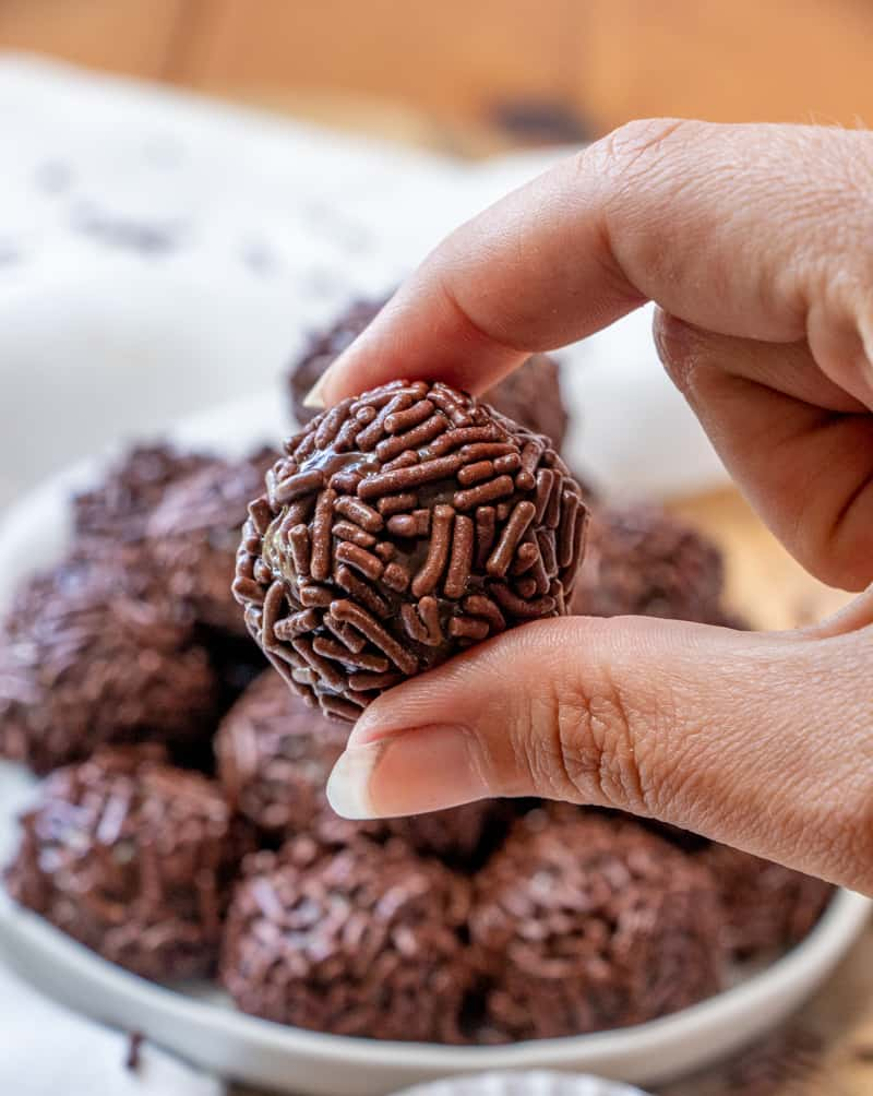 hand holding brigadeiro showing sprinkles up close