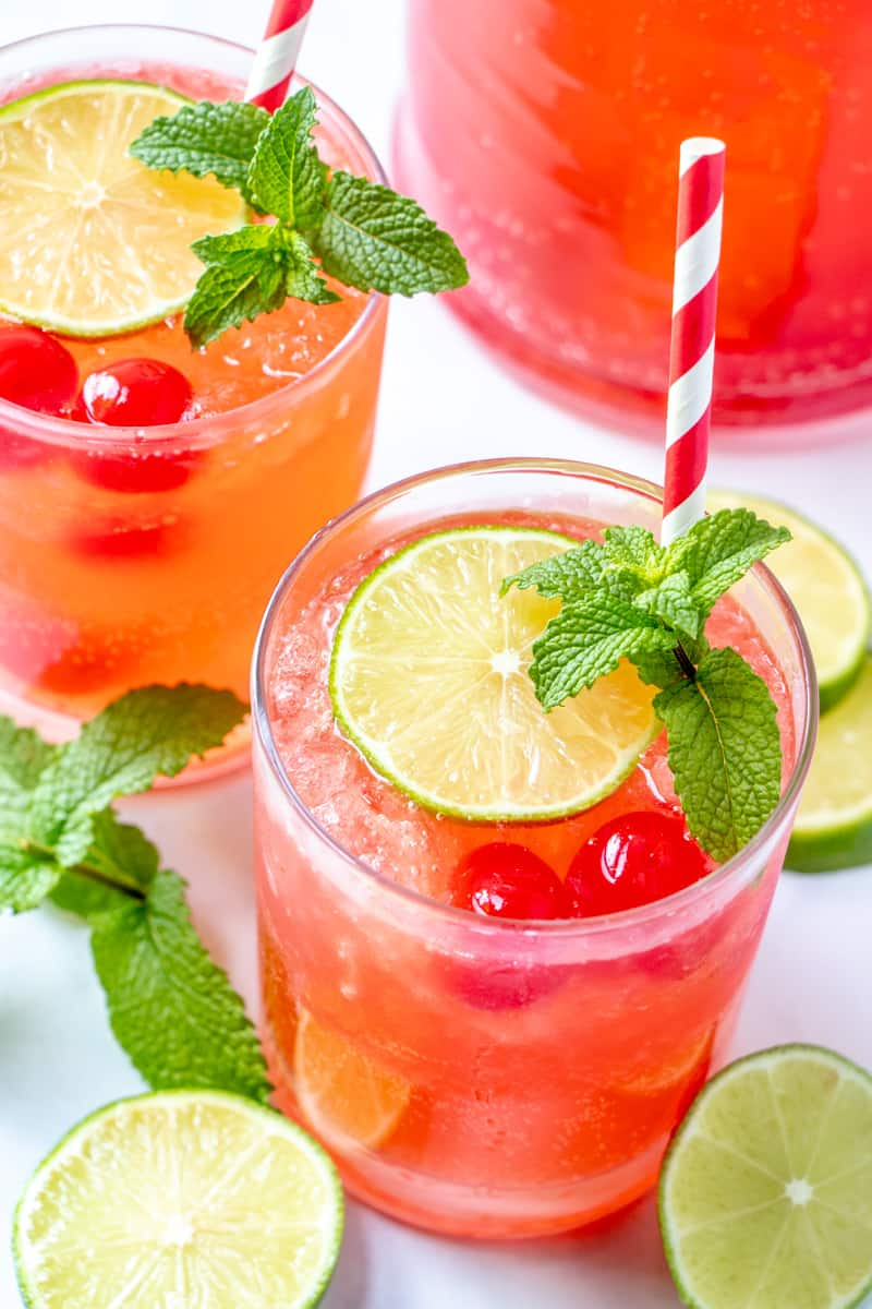 two glasses of cherry limeade with mint leaves and limes surrounding glasses
