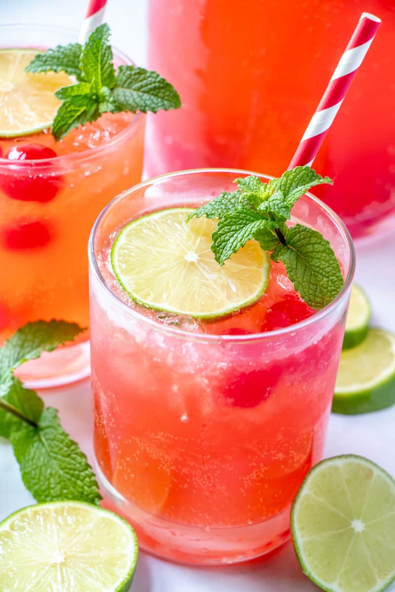 cherry limeade in glasses with limes cherries mint and swirled red straw