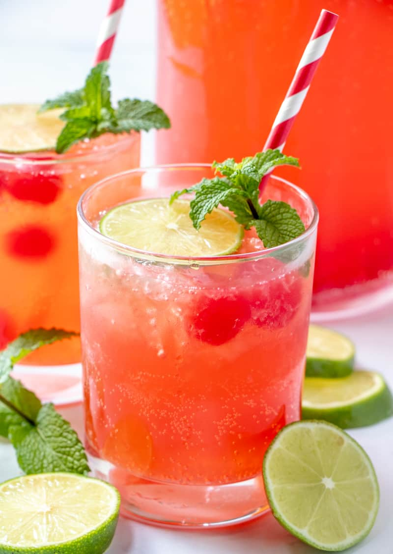 Fizzy cherry limeade in glasses with limes around glass and mint leaves