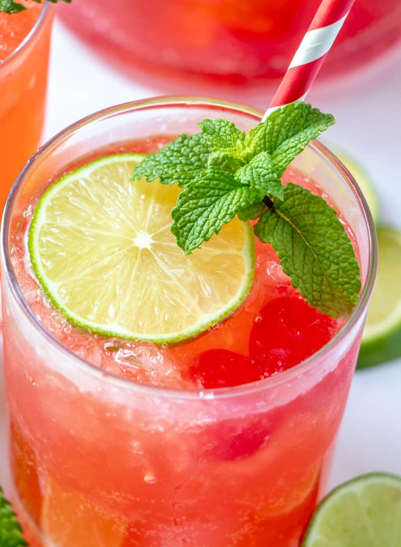 overhead photo of cherry limeade in glass close up with limes, mint, ice and cherries