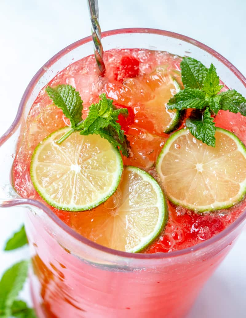 Cherry limeade recipe in pitcher garnishes with limes and mint leaves