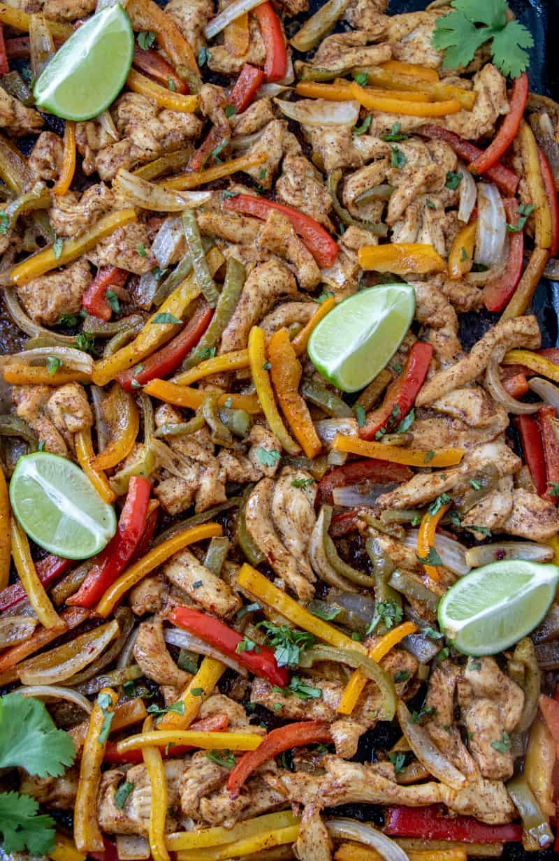 Sheet pan chicken fajitas on pan with lime wedges and cilantro cooked
