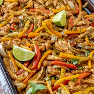 Sheet pan of chicken fajitas garnished with lime wedges and cilantro