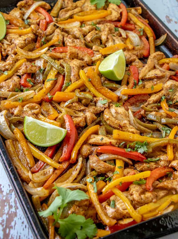 Sheet pan chicken fajitas at an angle on pan with limes and cilantro