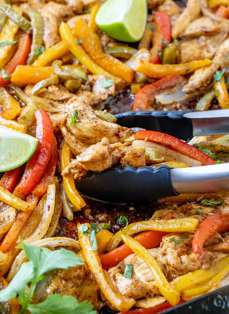 tongs picking up slices of chicken and peppers off of sheet pan