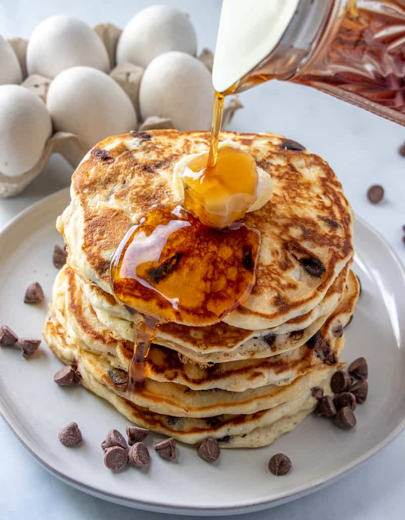 Stacked chocolate chip pancakes with syrup being poured over the top with pat of butter
