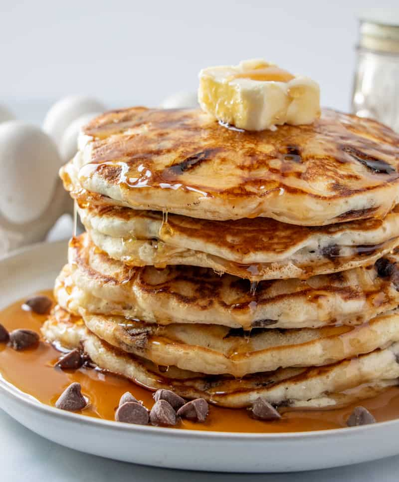 Side view of stacked chocolate chip pancake recipe with dripping syrup