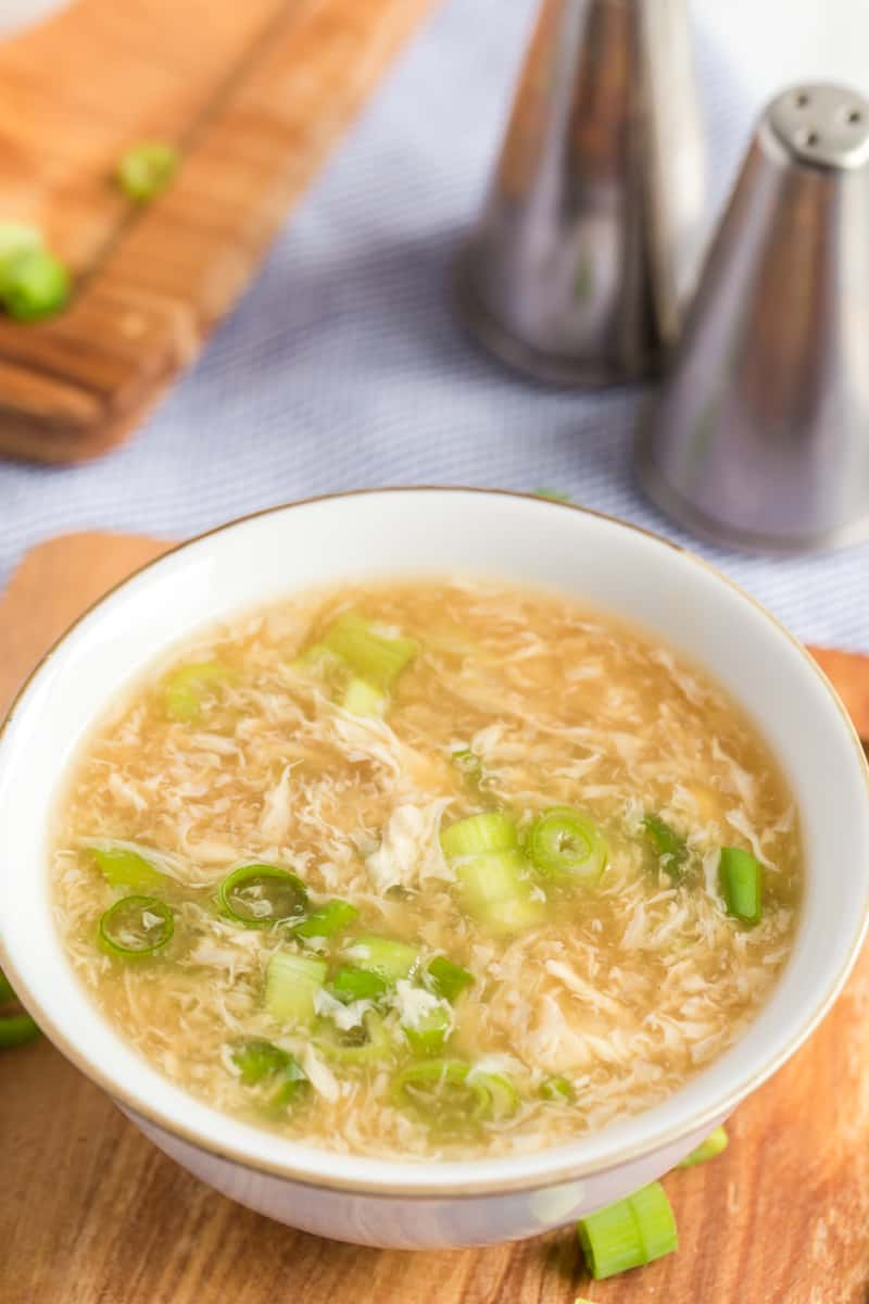 Egg drop soup recipe in bowl with egg stands and sliced green onions