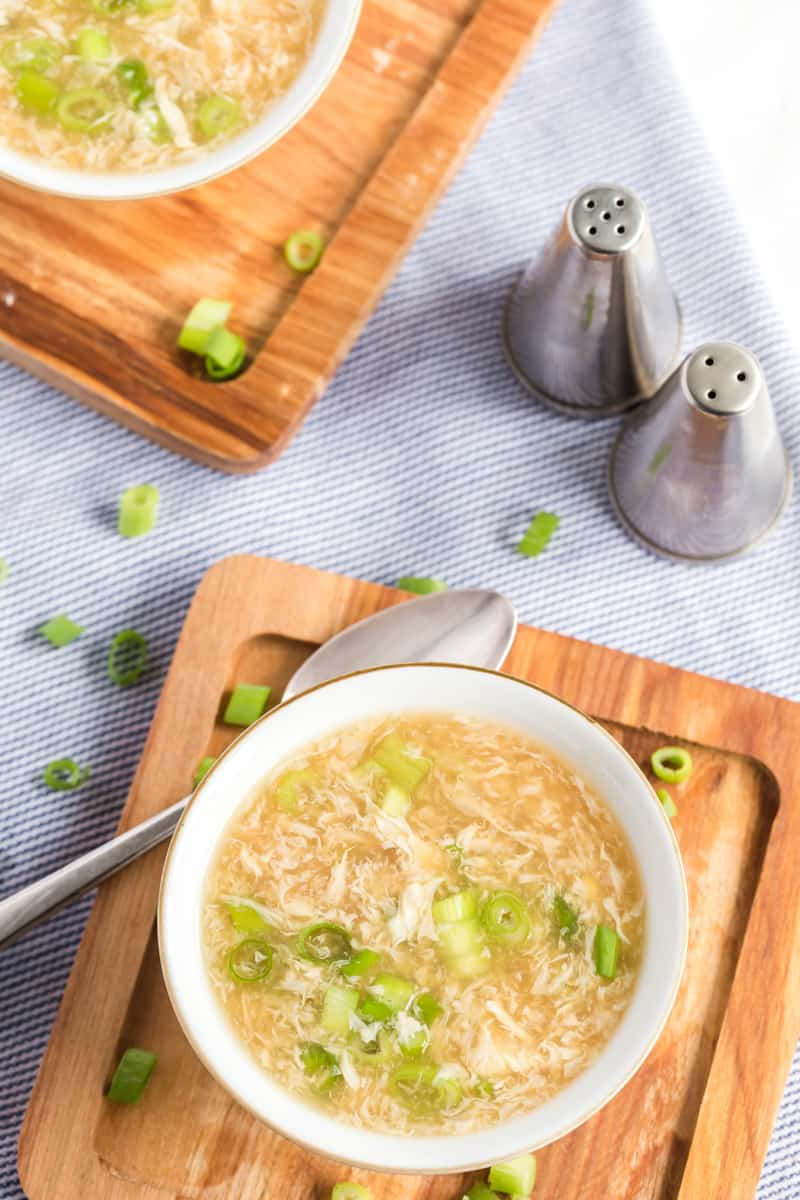 Overhead photo of egg drop soup recipe in bowls with salt and pepper shakers