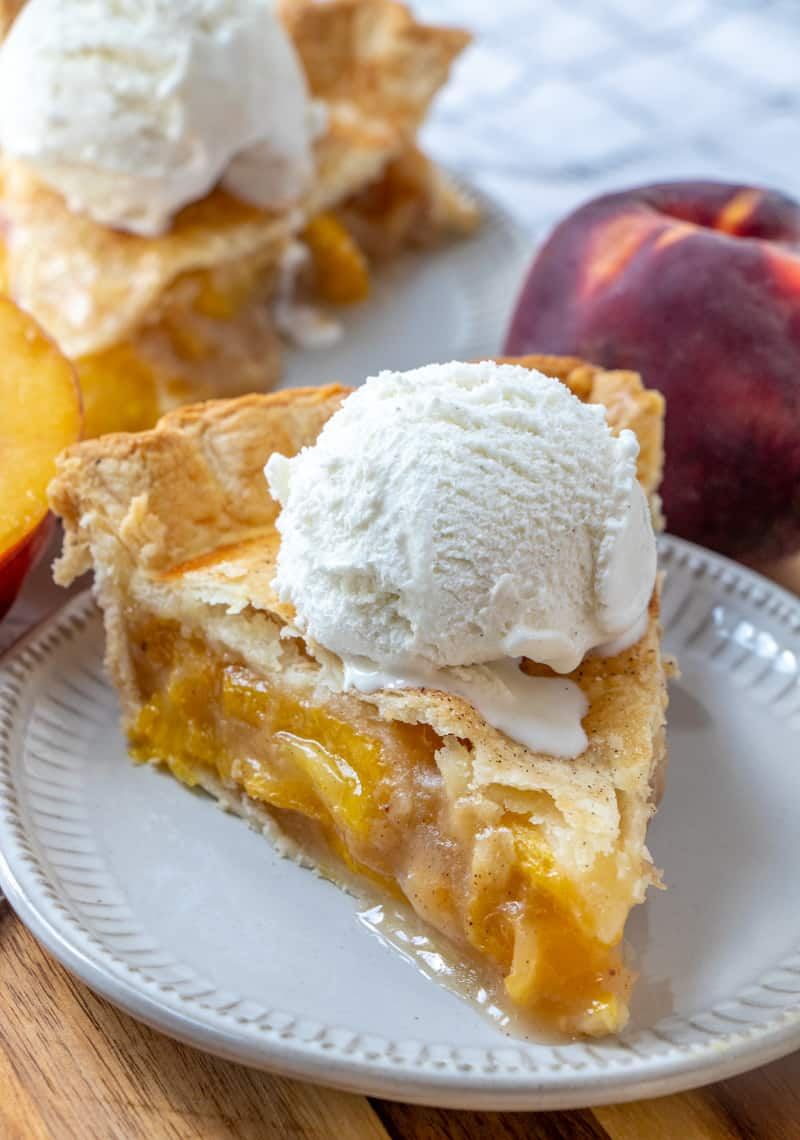 slice of peach pie on plate with vanilla bean ice cream on top with peach in background