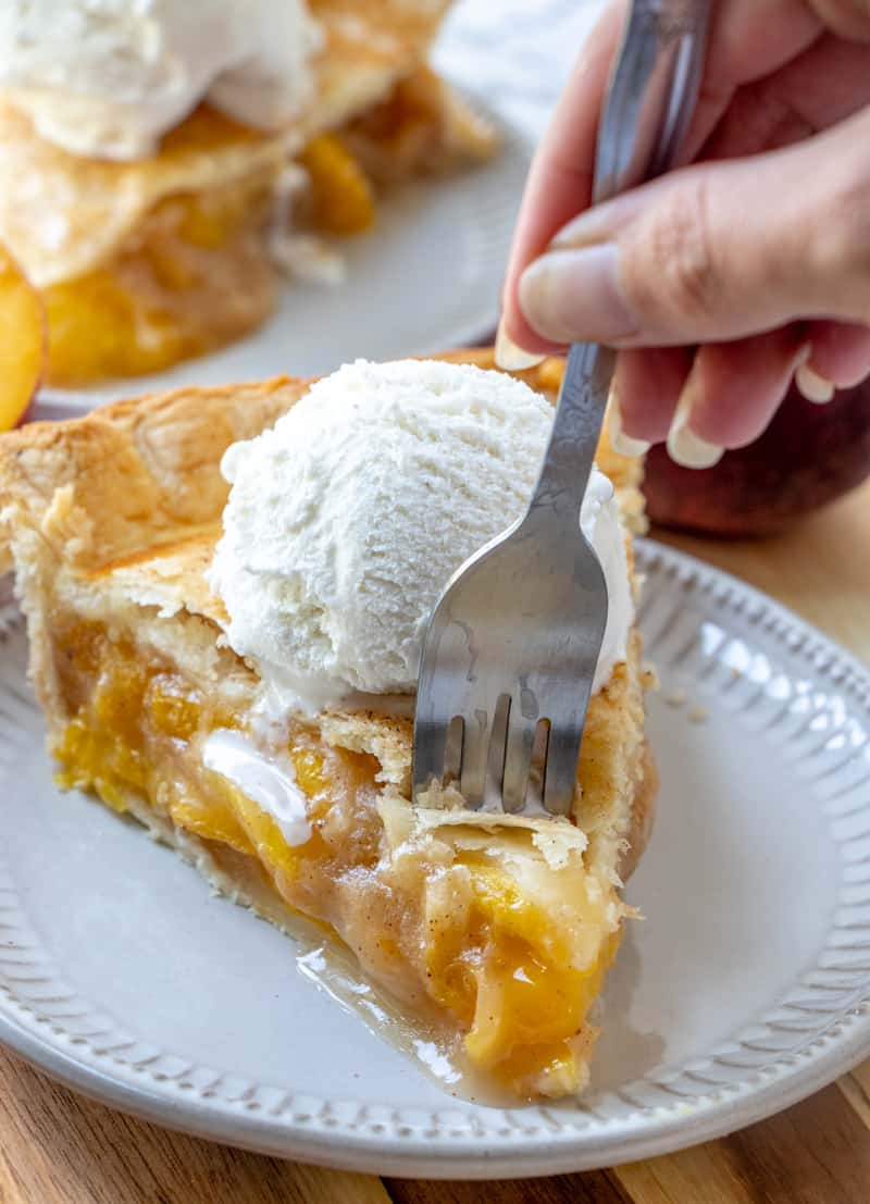 fork going into peach pie and ice cream on plate
