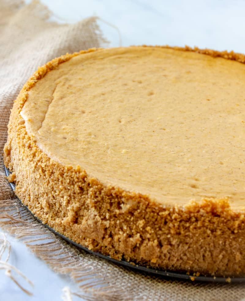 Full cheesecake uncut on table with burlap