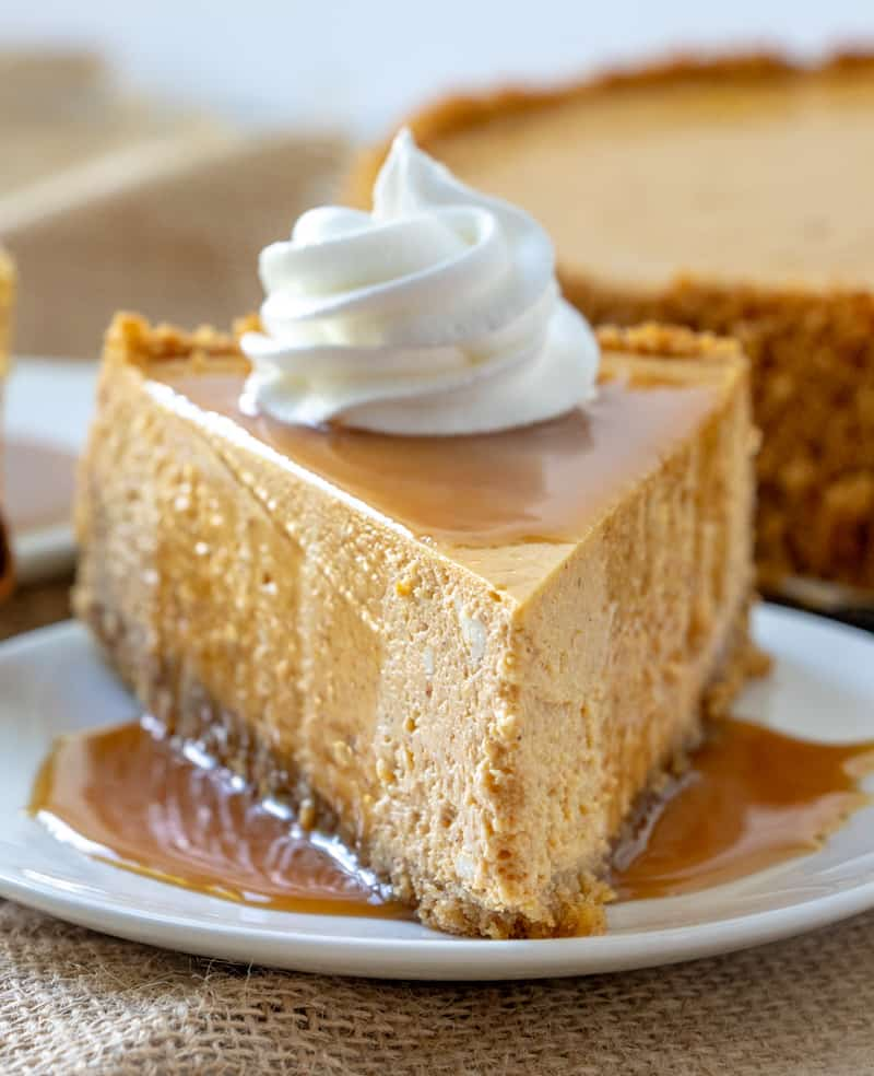 Pumpkin cheesecake slice on plate with caramel drizzle and swirl of whipped topping