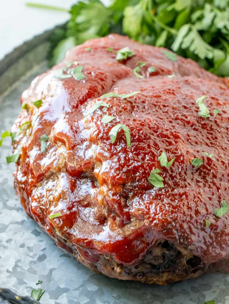 Up close photo of crockpot meatloaf glaze caramelized with parsley on top, uncut