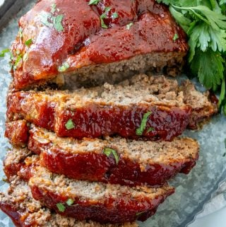 Sliced meatloaf garnished with parsley on metal serving tray