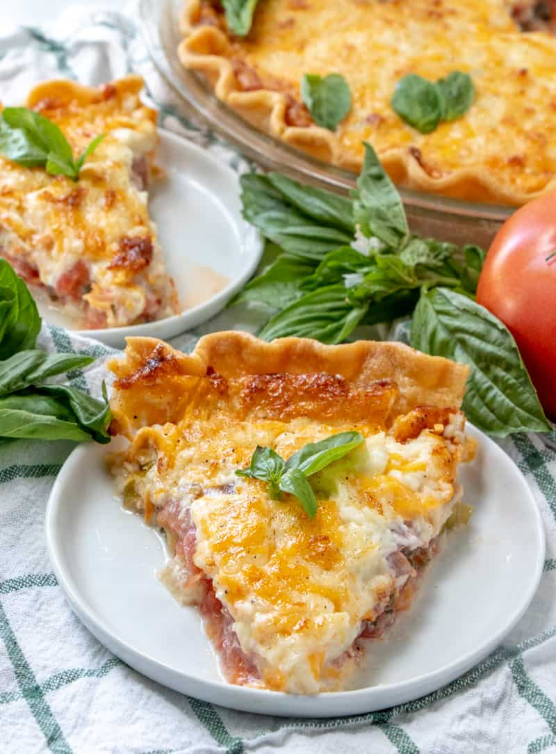 Slightly overhead photo of slice of tomato pie with basil leaf on top with another slice of pie in background