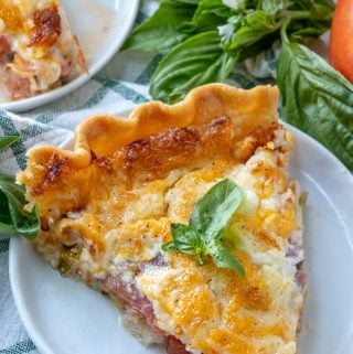 Slice of tomato pie on white plate topped with basil