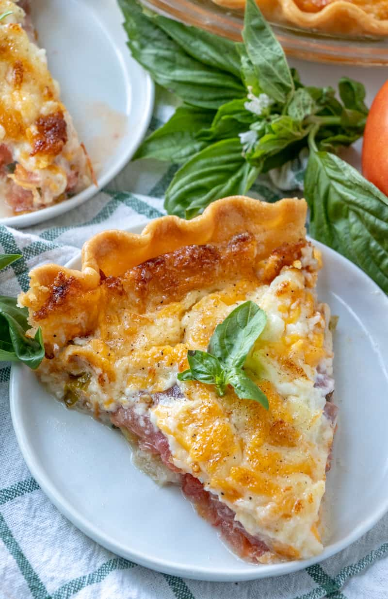 Tomato pie slice on plate topped with a basil leaf and surrounded by basil bunches