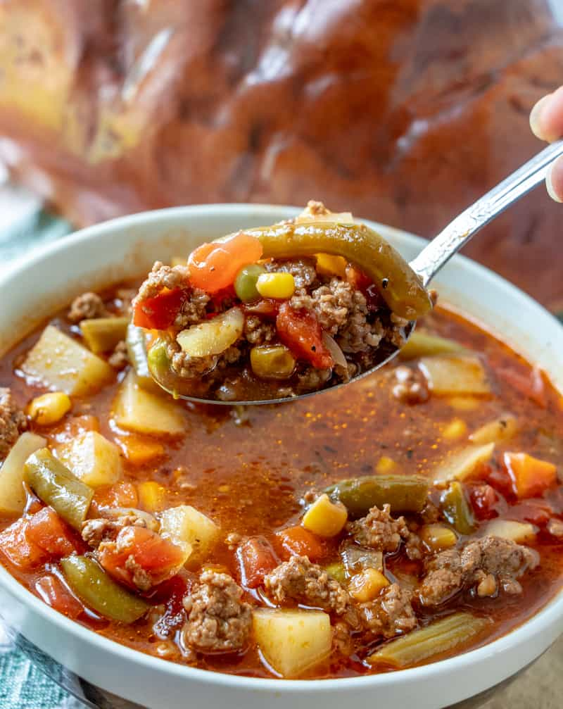 Soup spoon holding soup with vegetables and beef