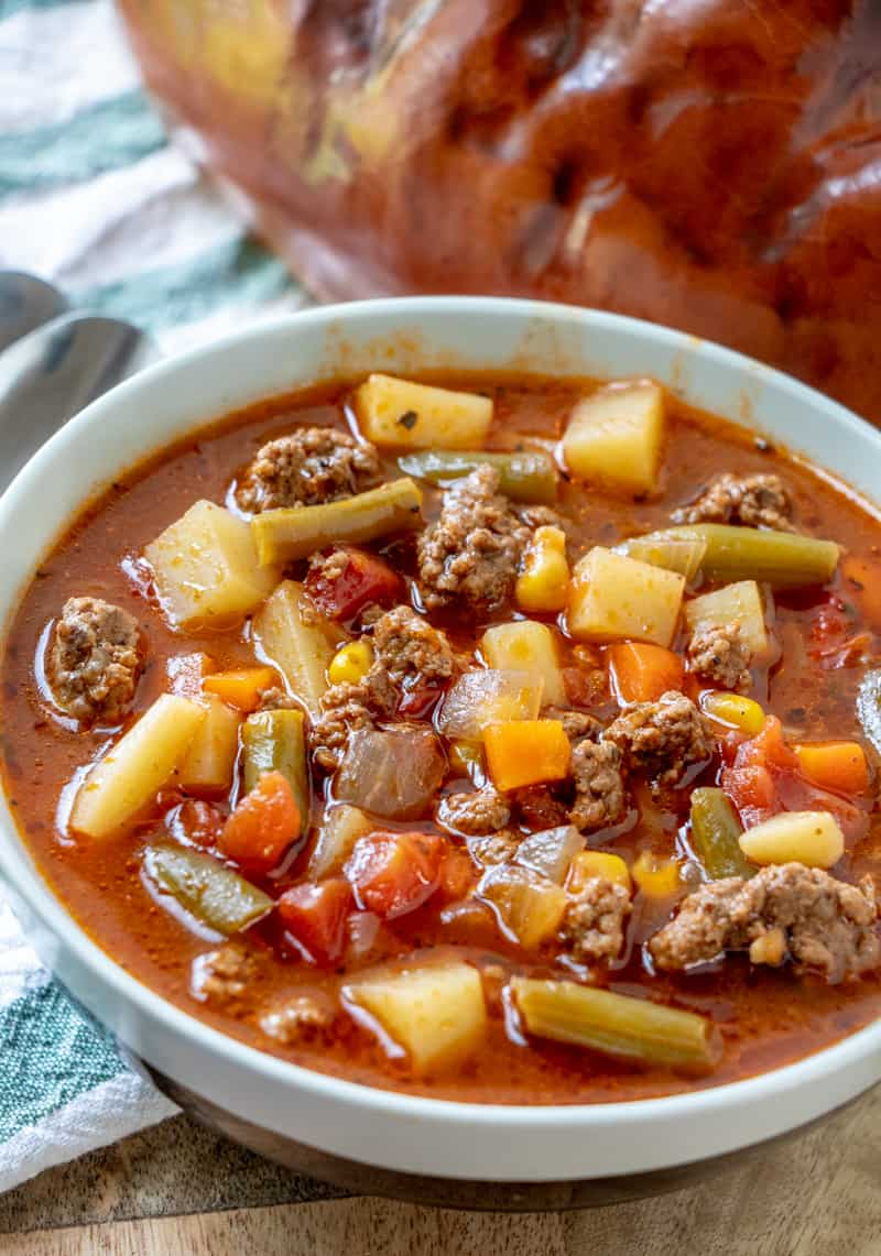Beef Vegetable Soup in bowl with bread in background