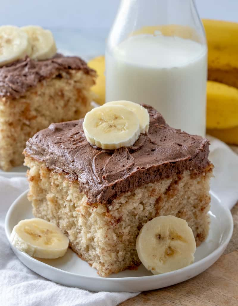 Slice of Easy Banana Cake on white plate with banana slices and milk behind cake