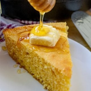 Cornbread on plate being drizzled with honey