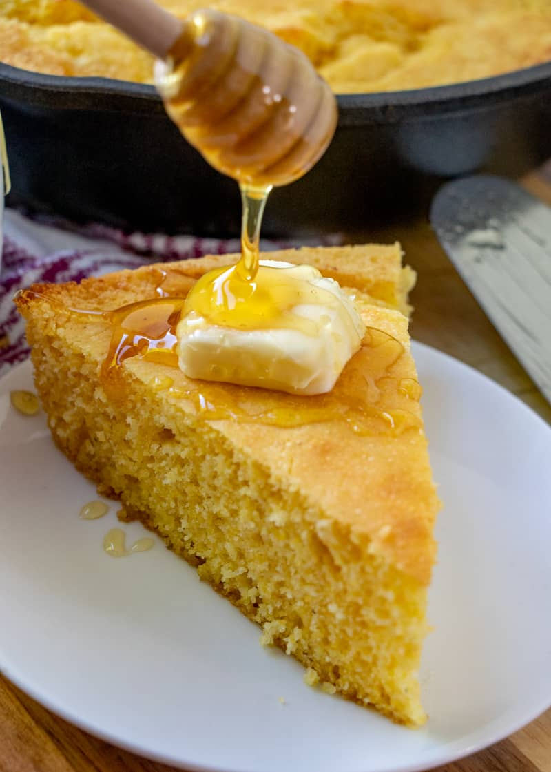 Honey being drizzled over pat of butter on slice of cornbread