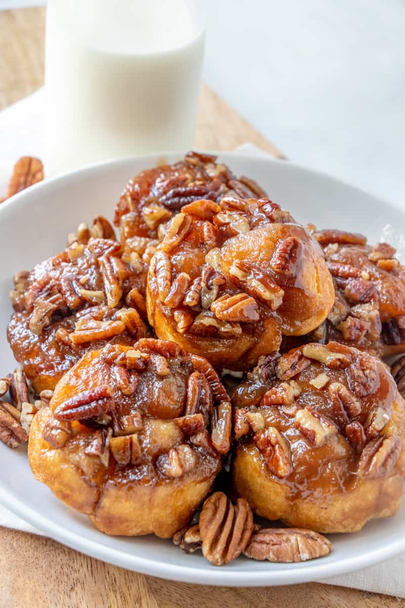 Easy Pecan Sticky Buns in shallow bowl glazed with chopped pecans on top