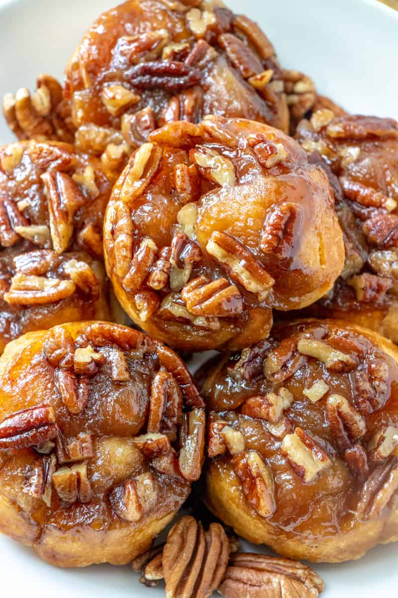 Up close photo of sticky buns stacked showing caramel glaze and pecans