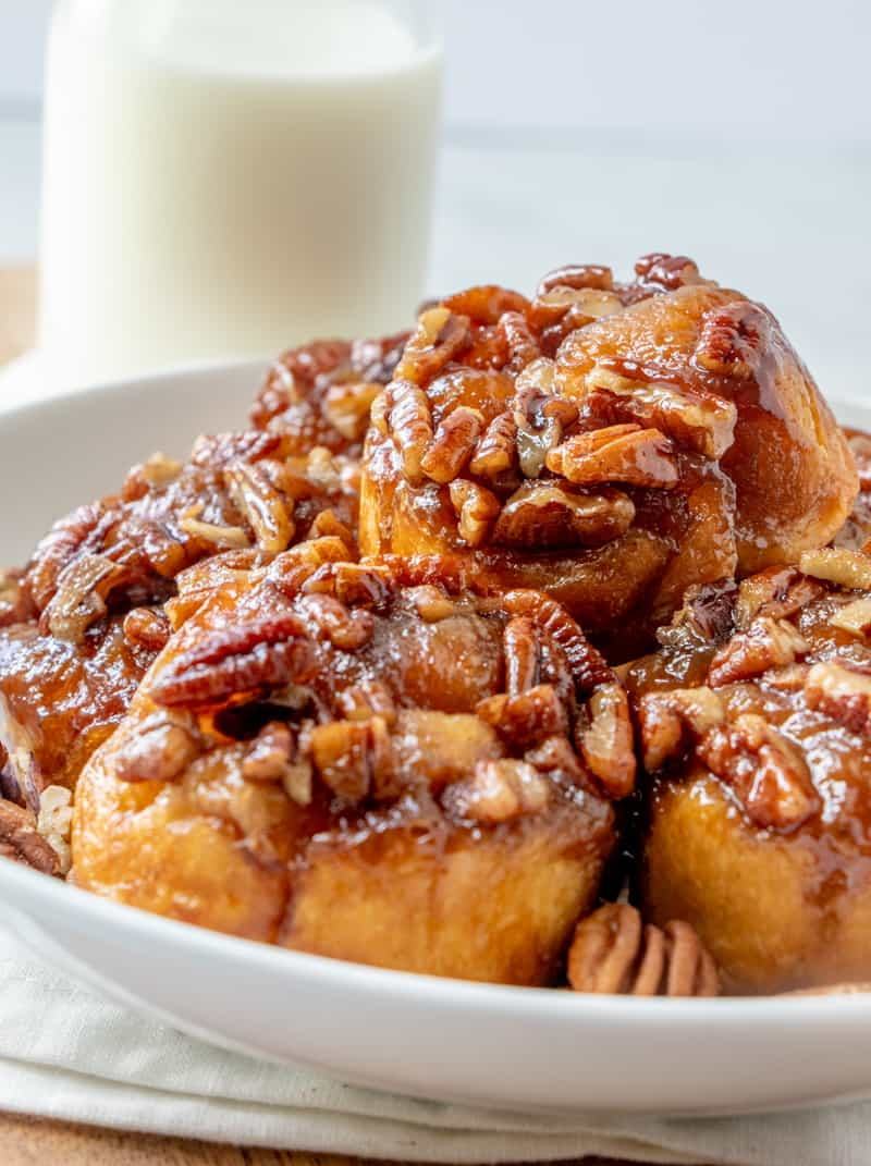 Sticky Buns in shallow bowl side photo of buns stacked with pecans and milk in background