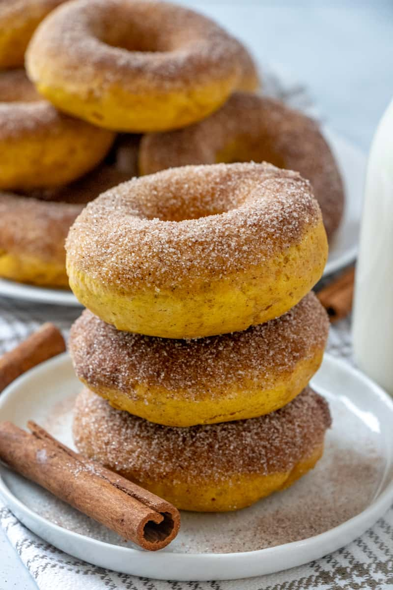 Side view of pumpkin donuts stacked on plate