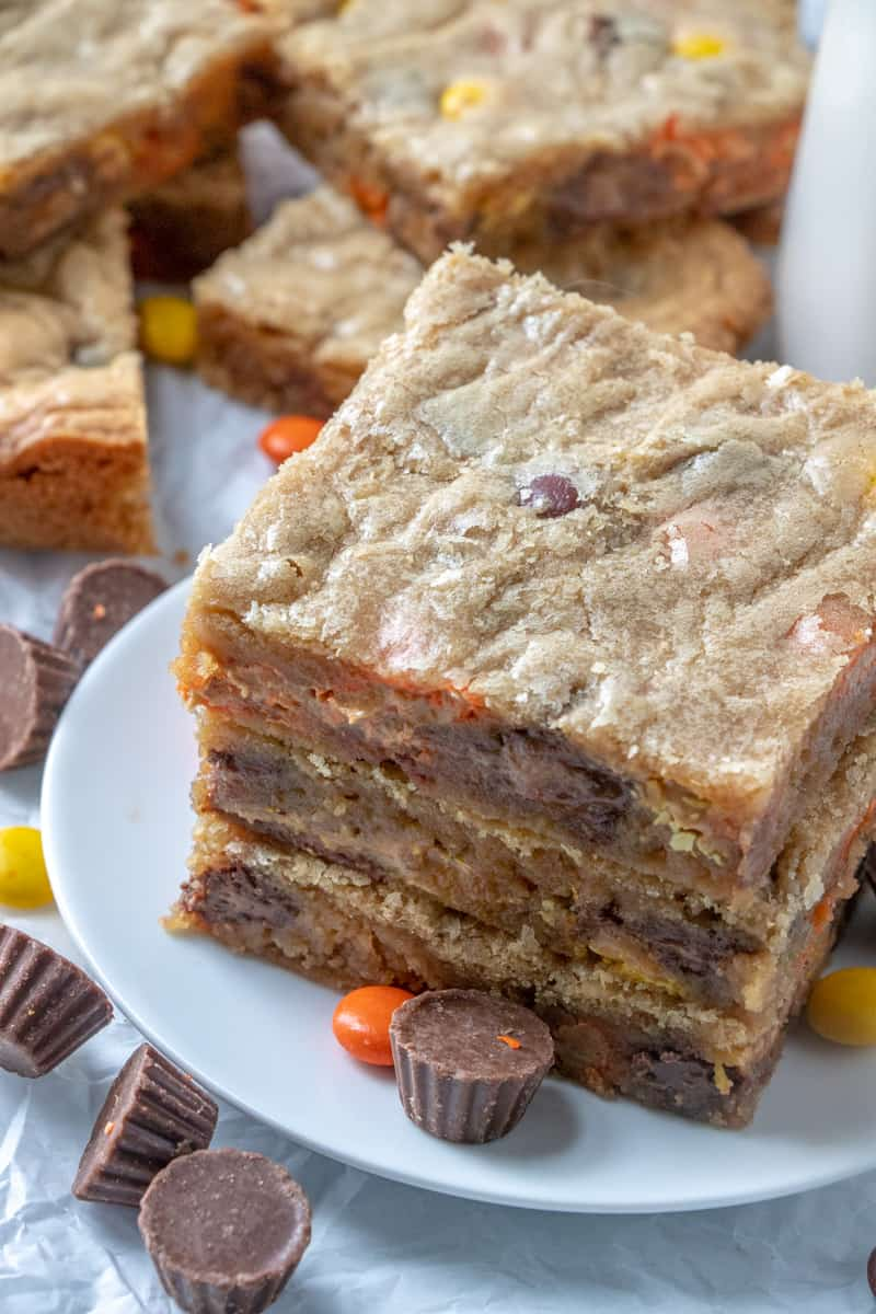 Overhead photo of stacked Reese's Peanut Butter Bars on plate with a pile of bars in background
