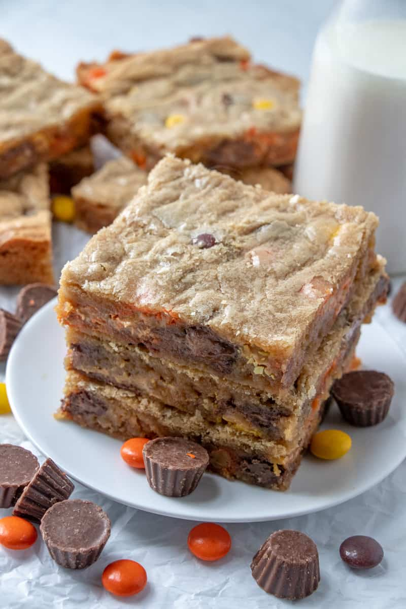 Reese's Peanut Butter Bars on plate with milk in background along with other cut bars