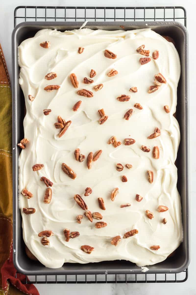 Overhead photo of frosted spice cake in pan with cream cheese frosting and pecans