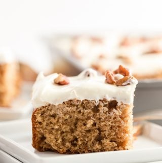 Plated slice of spice cake topped with chopped pecans